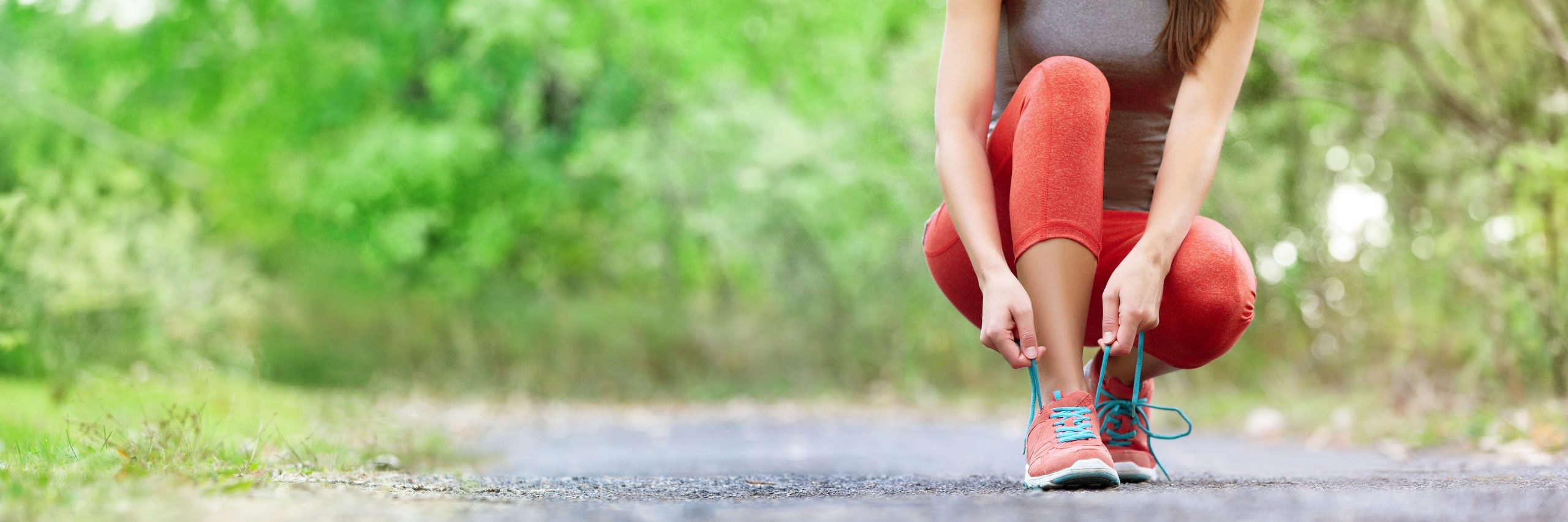 woman tying her shoe to prepare for exercising