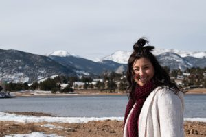 Happy woman smiling while standing in front of a mountain lake