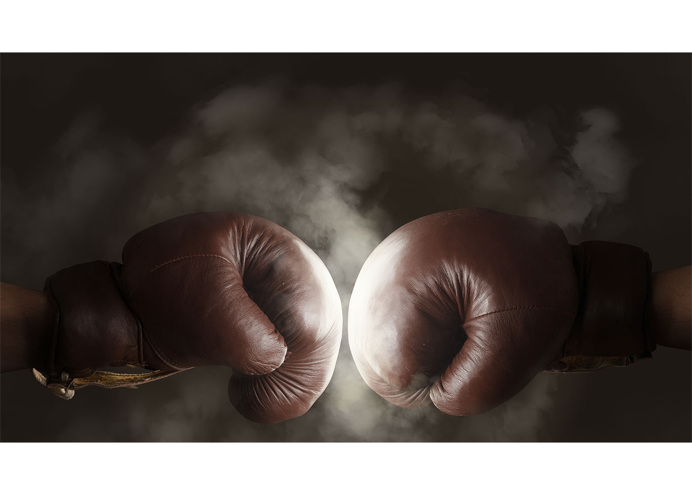 two boxing gloves meeting in a punch and emitting dust with a dark background
